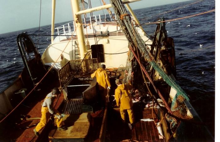 3 vissers op het dek in oliejas en -broek