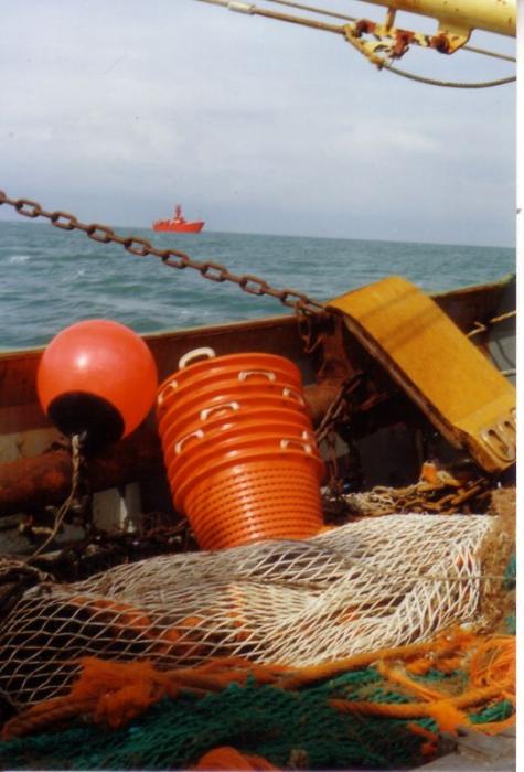 Vissersvaartuig vaart voorbij aan lichtschip