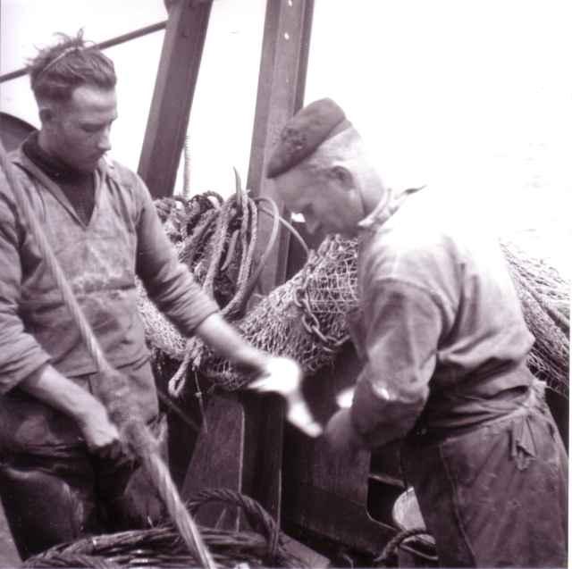 Vissers aan boord met netten en manden