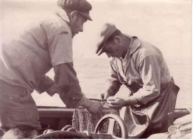 Ren� Savels (rechts) en andere visser herstellen garnaalnetten