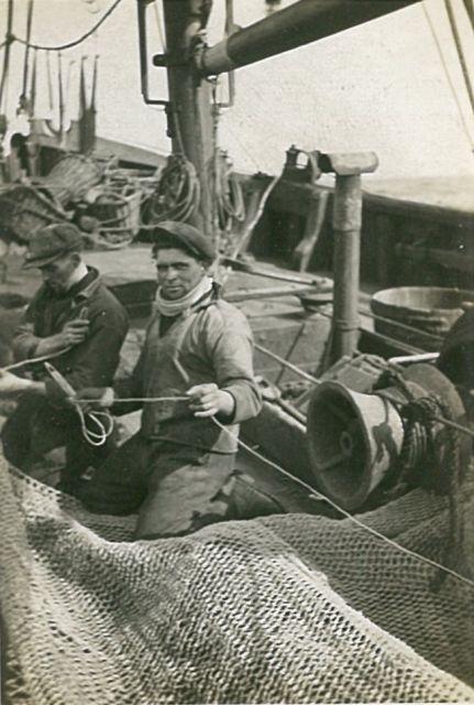 Vissers aan boord in de weer met touwen