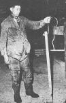 """Eind jaren 1950: Een arbeider van de kwekerij van """"Halewyck & Cie"""" in de Spuikom. Het onderschrift bij deze foto luidde: """"Aan zulke stokken, van een zware houtsoort die niet op het water drijft, worden de jonge oesters met behulp van cement vastgezet, om daarna in het water te groeien."""""""