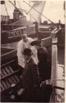 Doop vissersvaartuig met pastoor, meter en peter van het vaartuig
