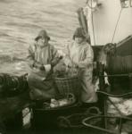 Vissers met olierok en zuidwester gutten vis
