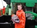 Jongen in oliejas met grote vis