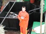 Jongen in oliejas en -broek met vis