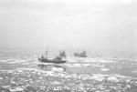 Twee vissersschepen tussen de ijsschotsen in de kustwateren (net uit de haven van Zeebrugge richting Blankenberge) tijdens de strenge winter 1962-1963. Het voorste schip is de Z.523 Jeanne-Madeleine. Het achterste schip is niet herkenbaar.