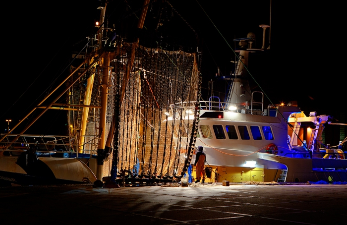 Vlissingen, Holland.  Fisherman taking a break while working on repairs to the pulse nets on the Dutch trawler 'Boeier' in the harbour.