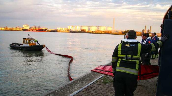 Uitleggen van band om olie af te dammen rond het schip
