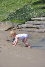 Spelend jongetje bij strandhoofd